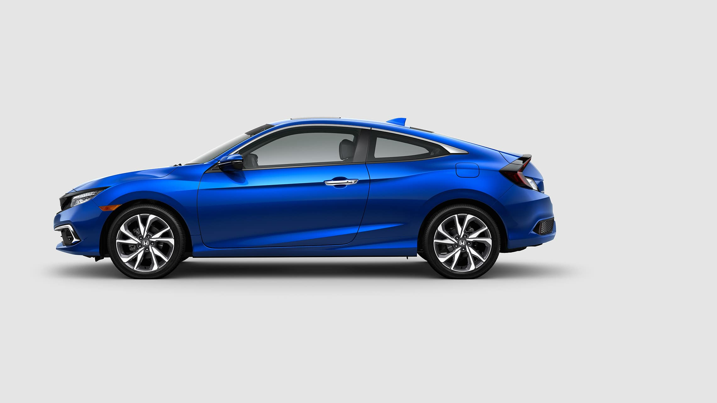 Driver-side view of the 2020 Civic Touring Coupe in Aegean Blue Metallic.