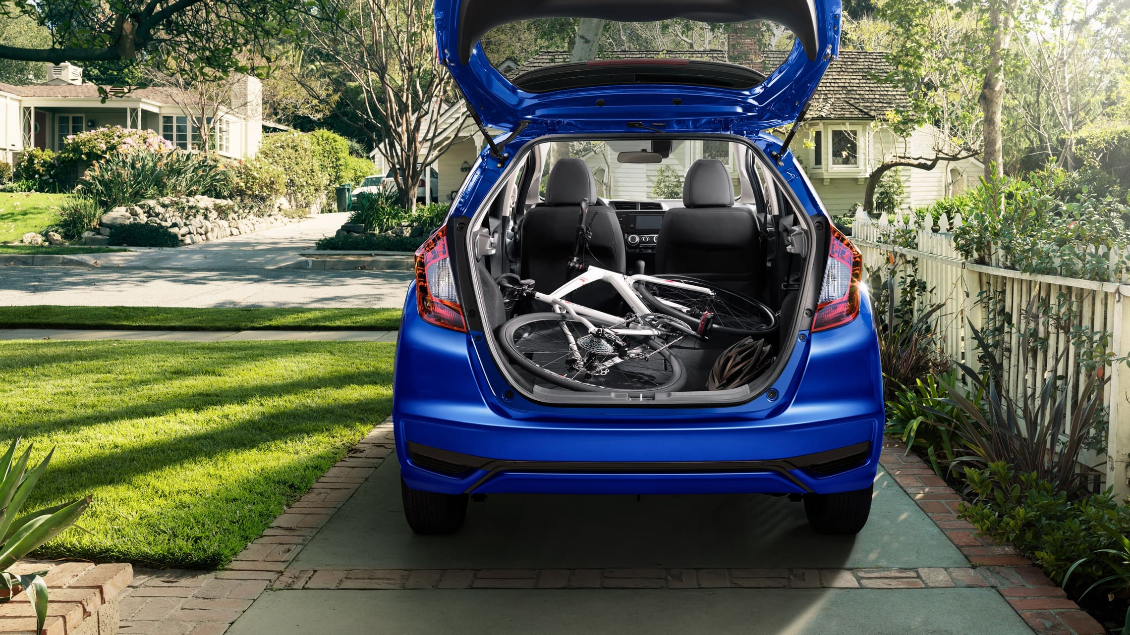 Exterior rear view of the 2020 Honda Fit EX-L in Aegean Blue Metallic with liftgate open and bicycle in cargo area.