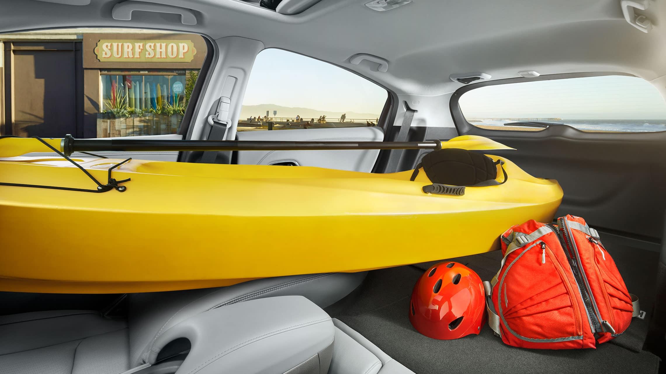 Interior view of the 2020 Honda HR-V Touring with Gray Leather, with all rear seats and passenger seat folded down, storing a kayak and luggage.