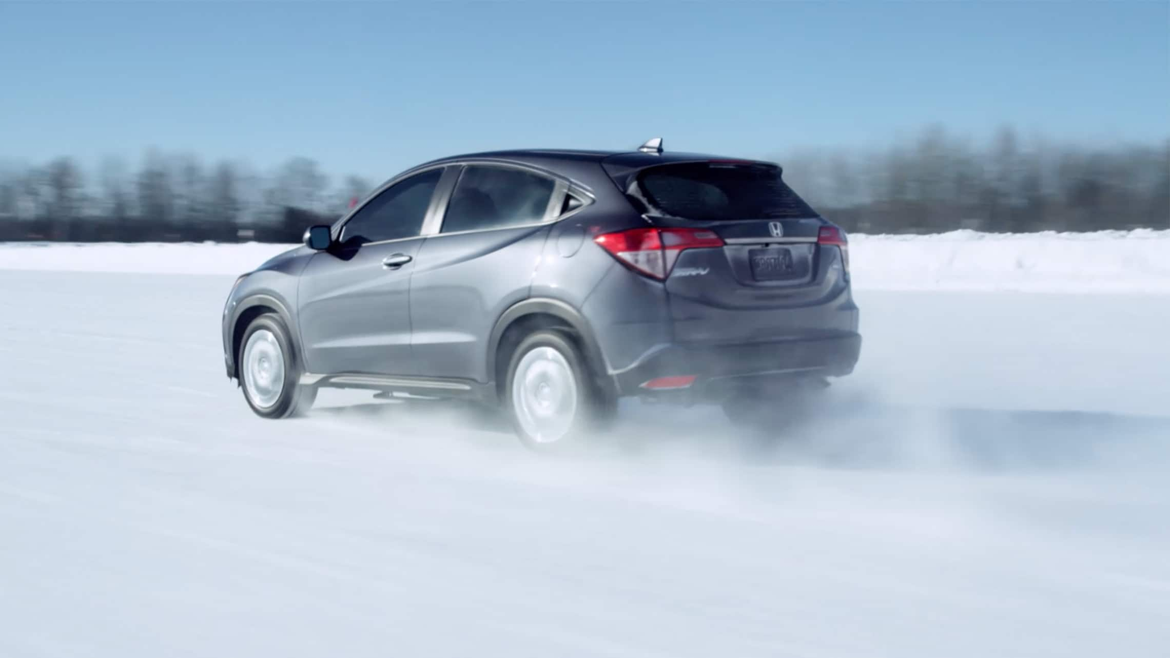 Rear driver-side view of the 2020 Honda HR-V LX in Modern Steel Metallic on snow-covered road.