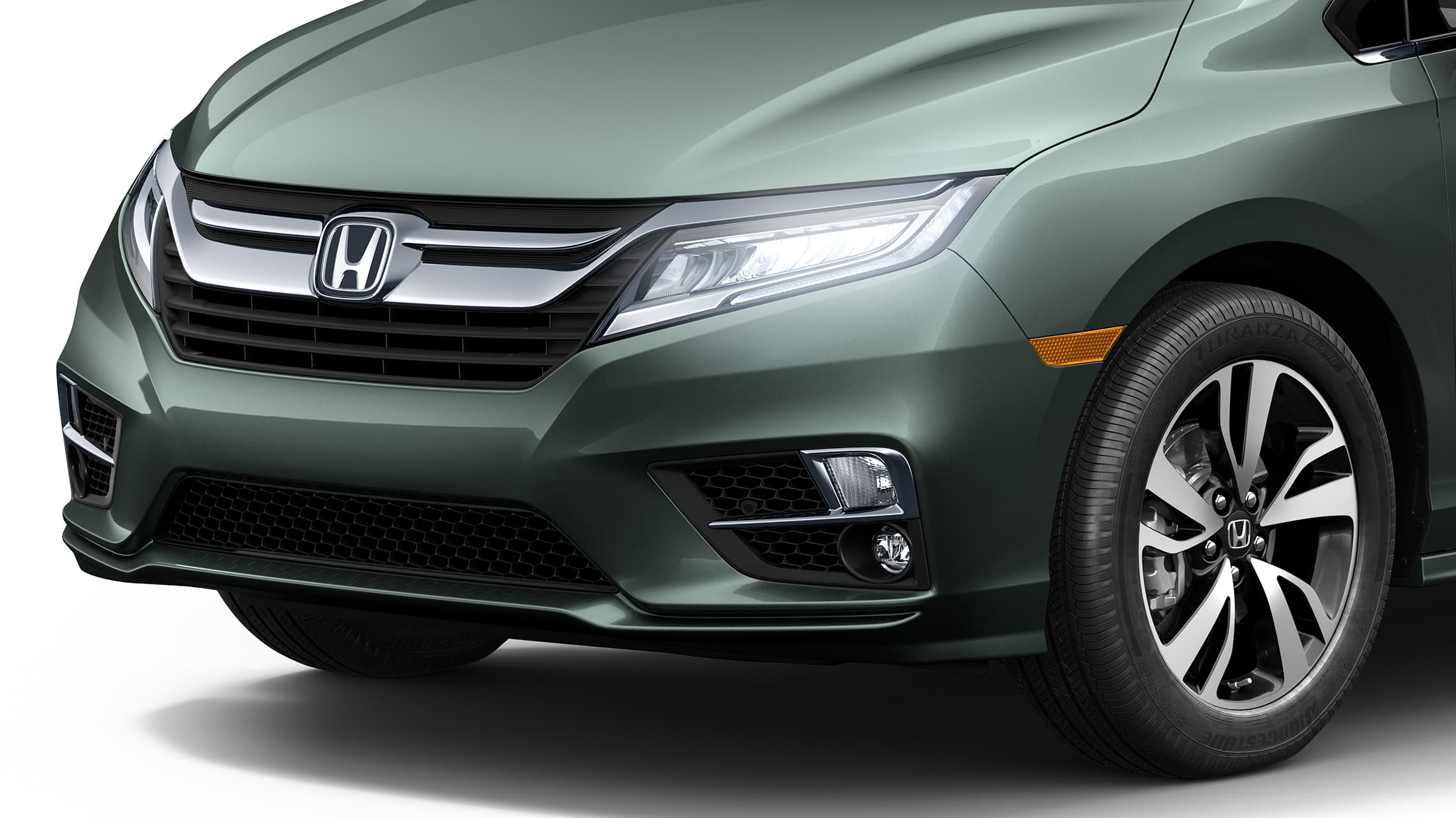 Front 3/4 driver-side close-up of headlights on 2020 Honda Odyssey Elite in Forest Mist Metallic.