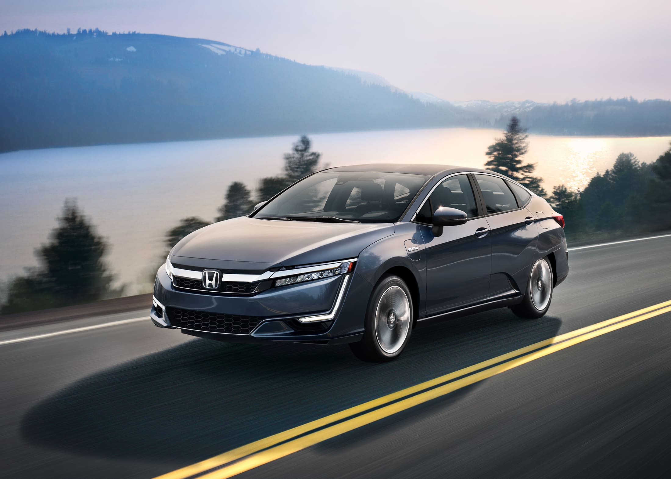 The Clarity Plug-In Hybrid is shown in Modern Steel Metallic driving past a body of water.