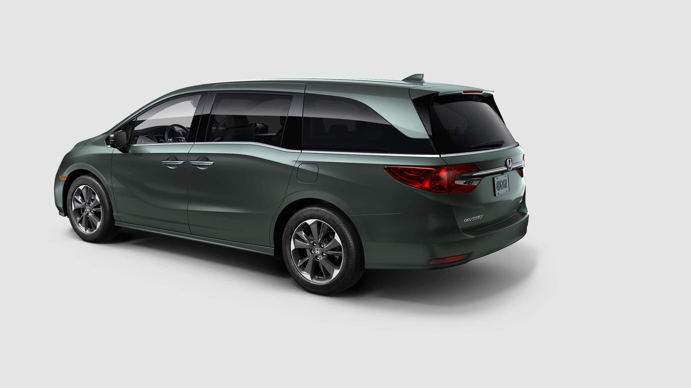 Rear driver-side view of the 2021 Honda Odyssey Elite in Forest Mist Metallic.