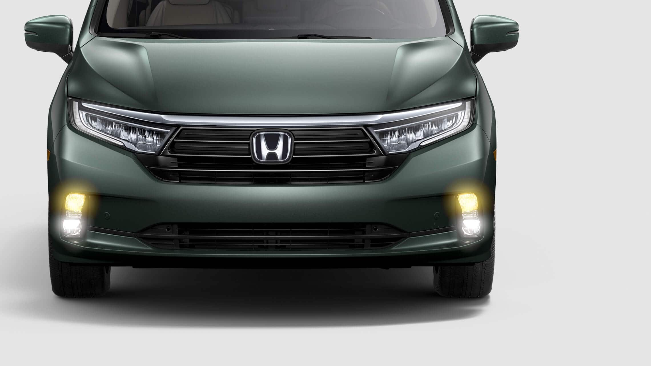 Front close-up view of driver-side headlight on the 2021 Honda Odyssey Elite in Forest Mist Metallic.