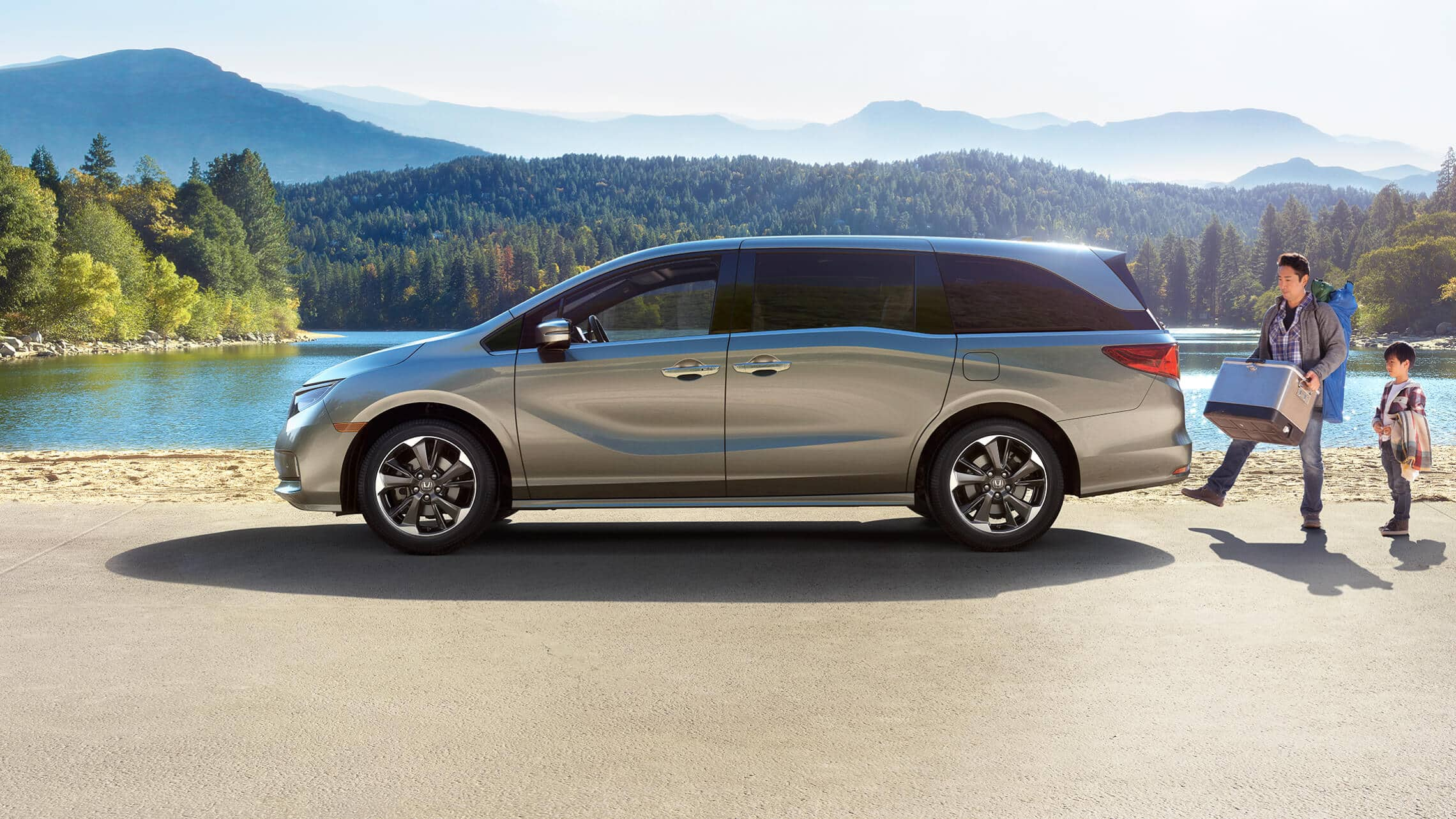 Driver-side profile view of the 2021 Honda Odyssey Touring in Lunar Silver Metallic parked in forest environment.