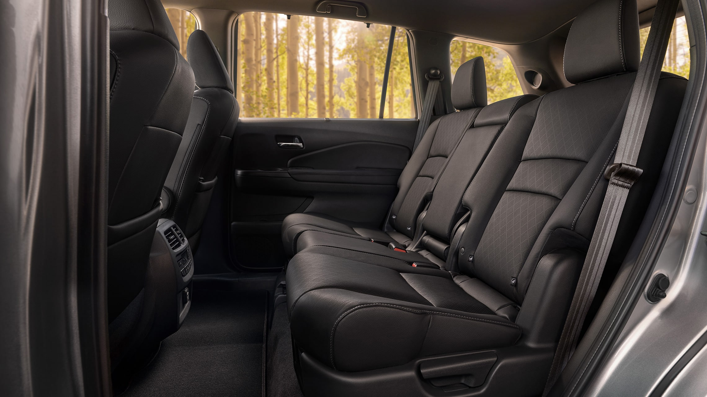 Driver-side profile view of the second-row seats in the 2021 Honda Passport Elite with Black Leather.