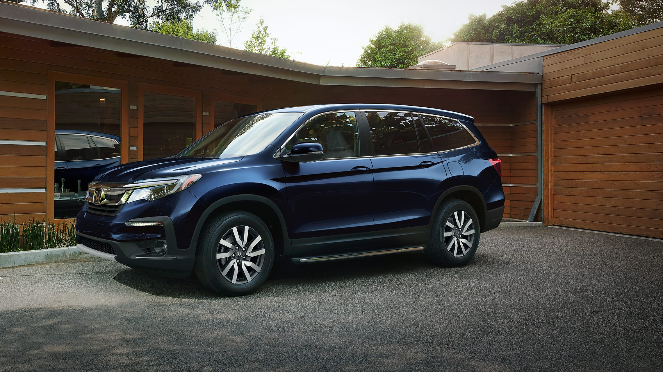 Front 7/8 driver-side view of 2021 Honda Pilot EX-L in Obsidian Blue Pearl parked outside a modern family home.