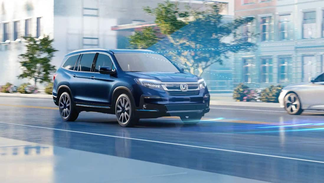 Rear 7/8 driver-side view of 2021 Honda Pilot Elite in Modern Steel Metallic displaying Honda Sensing® technology.